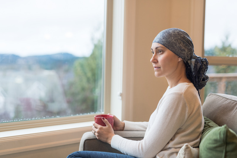 Beautiful breast cancer survivor sits by window wearing headscarf drinking tea.