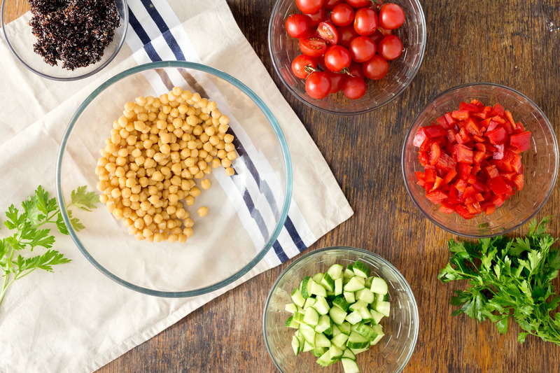 Fresh ingredients in glass bowls on a table including chickpeas, tomato and cucumber.