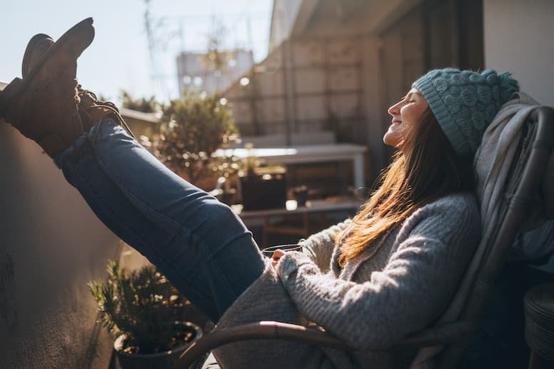 A young woman in a knit hat sits in the sun with her feet up, to help combat seasonal affective disorder.
