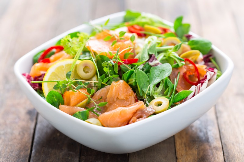 A leafy green salad loaded with fresh salmon, fruit and vegetables.