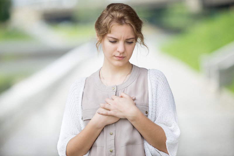 Woman with worried look on her face clutches her chest with AFib symptoms.