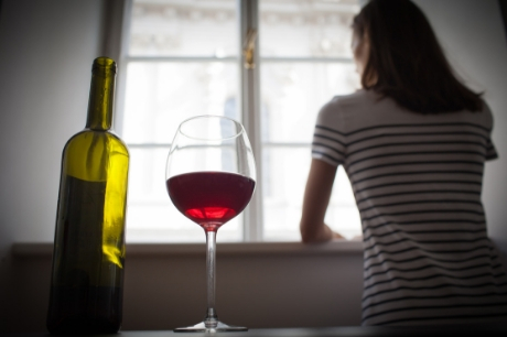 Women looks out of a window with a nearly empty wine bottle and glass of red wine on the table behind her.