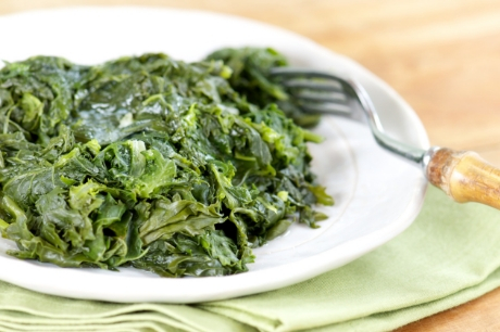 Quick collard greens cooked and served on a plate with a fork.