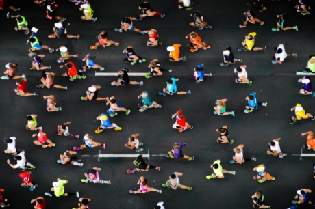 Overhead view of marathon runners on a three-lane street.