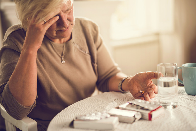 Older woman holding her head in her hand while about to take pain medication.
