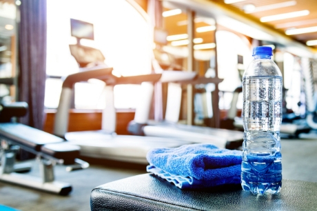 Water bottle and blue towel on a workout bench in an empty gym.
