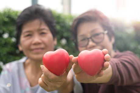 Older woman and adult daughter holding heart figures up in air