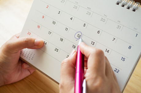 Female holding calendar, circling date when her ovulation cycle starts.