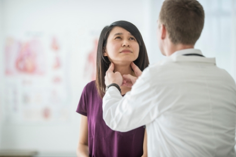 Woman getting her thyroid checked by a male doctor.