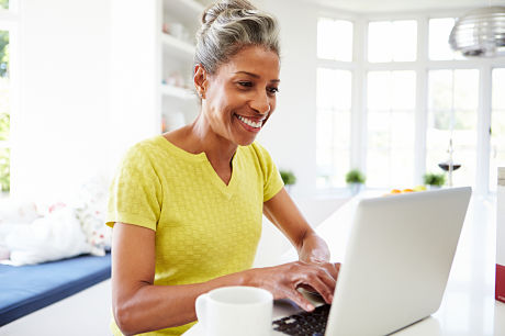 Middle-aged African American woman accessing myGeisinger from a laptop in her kitchen.