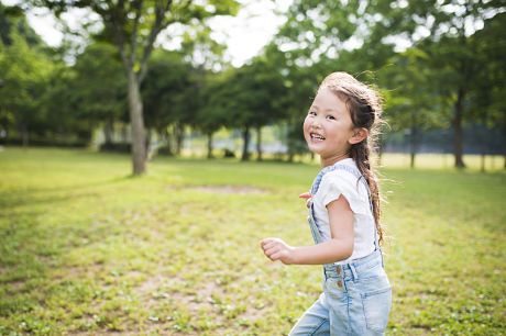 Little girl running and laughing outside during summer.