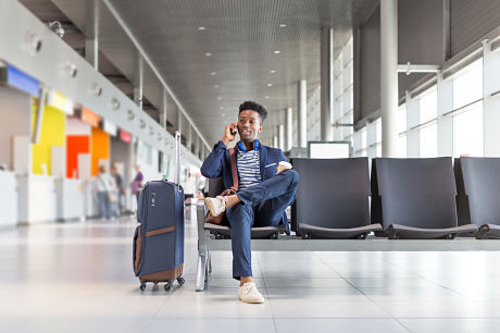Young man talking on the phone in an airport lounge.