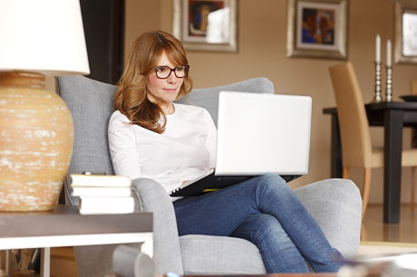 Middle-aged woman accessing myGeisinger on a laptop in her home.