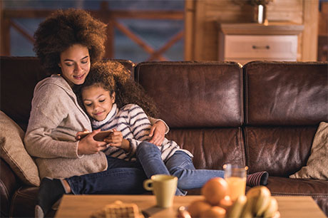 Happy African American mother and daughter relaxing on sofa in the living room and using mobile phone to access myGeisinger.