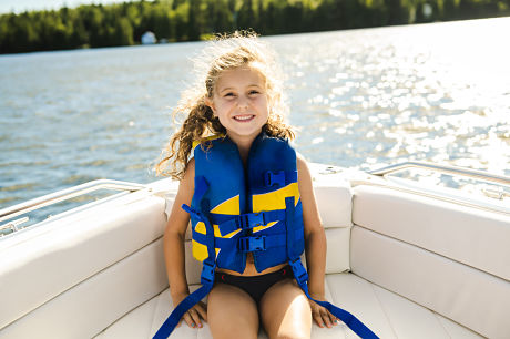 Little girl wearing a life jacket in a boat on the lake.