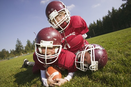 3 young football players in a pile