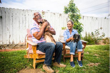 Older couple laughing and playing with their dog.
