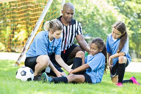 Soccer coach and referee tending a female player's injury