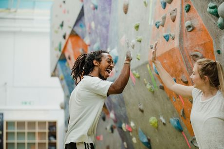 Two young adults rock climbing during recreation therapy.