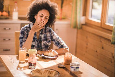 Woman feeling nausea and morning sickness during breakfast time at the kitchen table.