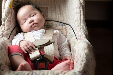 Infant fastened with seat belt for safety purpose in car seat going to well-baby visit.