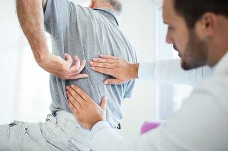 Doctor examines patient for back pain.