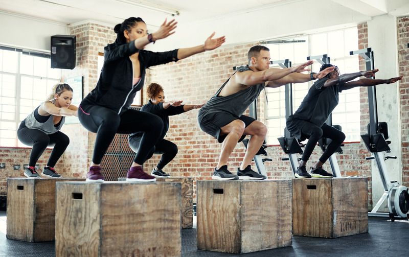 Shot of a focused group of young people jumping onto crates as exercise inside of a gym