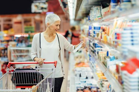 Woman reading food label shopping in a grocery store.