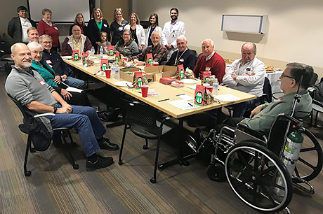 A group of cancer providers, staff and Road to Recovery drivers enjoy cookies at a holiday event