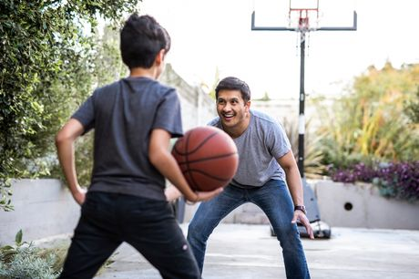 Healthy, active father and son playing basketball.