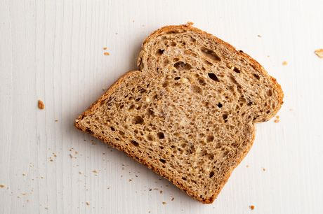 A slice of whole grain bread on a white background.
