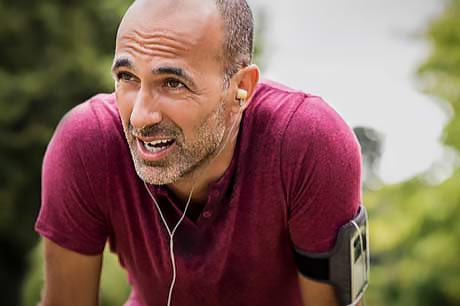 Man catching his breath after a run to combat stress