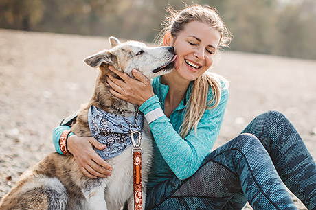 woman with urinary incontinence enjoying time outdoors with her dog
