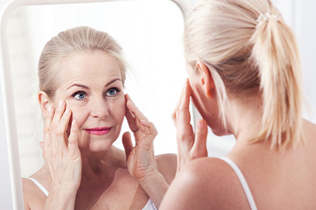 Woman looking in the mirror and considering Botox