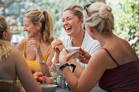 A group of middle-age women, laughing together at an outdoor cafe.