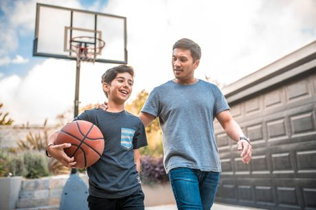 Father and son playing basketball in their driveway.