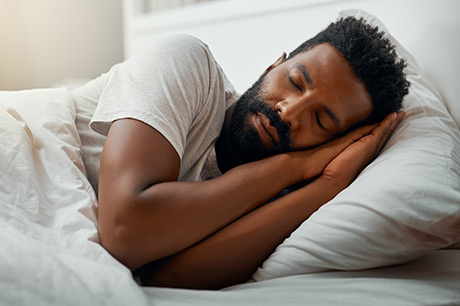 Man resting in bed recovering from COVID-19