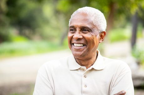 Older man smiling, outdoors.