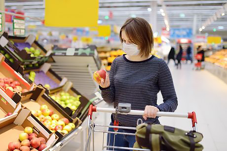 Woman grocery shopping safely to avoid the spread of coronavirus