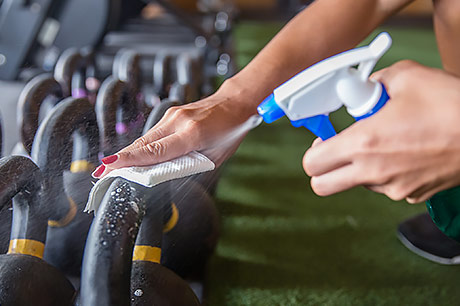 Cleaning gym equipment with disinfectant to prevent the spread of COVID-19.