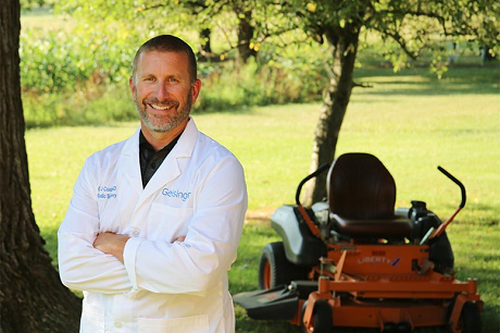 Orthopaedic surgeon Gerard Cush, MD, stands in front of his lawnmower at home.
