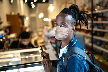 Young male wearing a mask in a neighborhood deli.