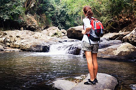 Woman hiking along a local waterway stops to enjoy a small waterfall.