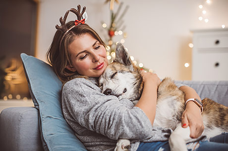 Getting a break from the holidays, a young woman relaxes by holding her dog on the couch.