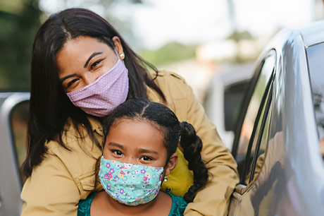 Mother and child wearing a mask in a store parking lot.