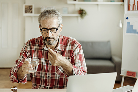 Man taking an aspirin at home