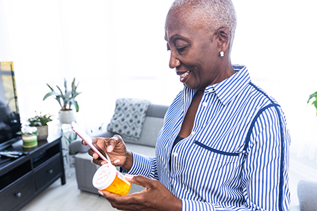 Woman using phone while holding prescription bottle