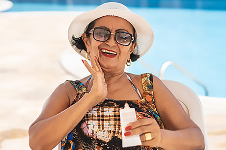 Senior woman applying SPF outdoors to protect from sun damage.