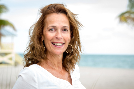 Mid 40s woman on a beach with clear skin