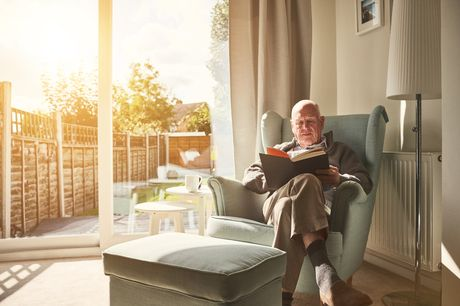 Older man sitting on a couch near a window reading a book.